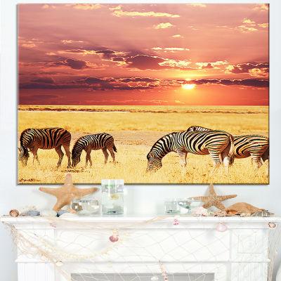 Designart Zebras Grazing Together At Sunset Canvas Art