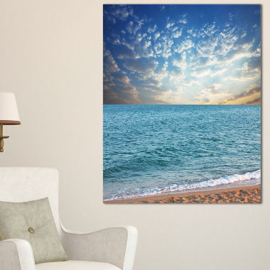 Designart Fasting Moving Clouds Over Blue Beach Canvas Art