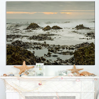 Designart Gloomy Sunset Over Rocks And Waves Canvas Art