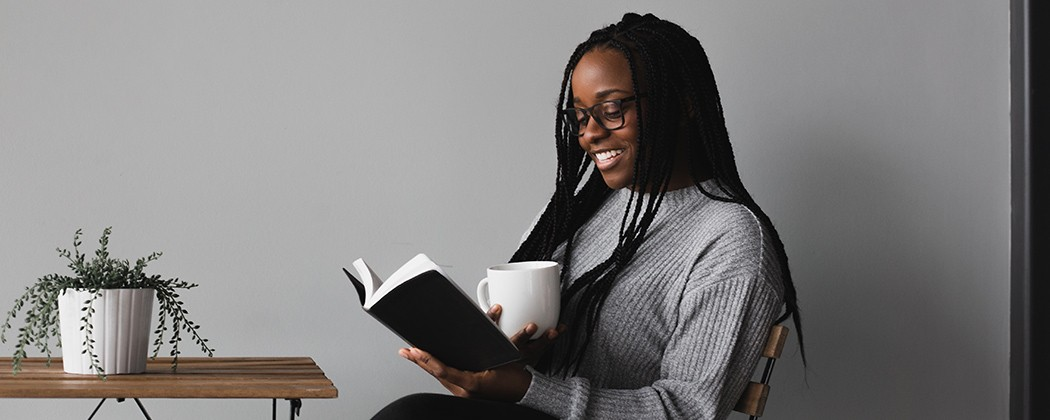 Woman reading a book with a smile