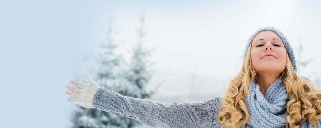 Young women with outstretched arms in the snow