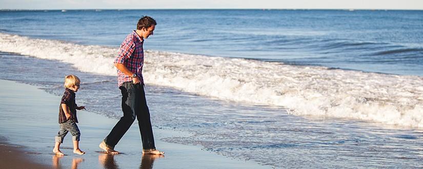 Man and boy walking along the beach