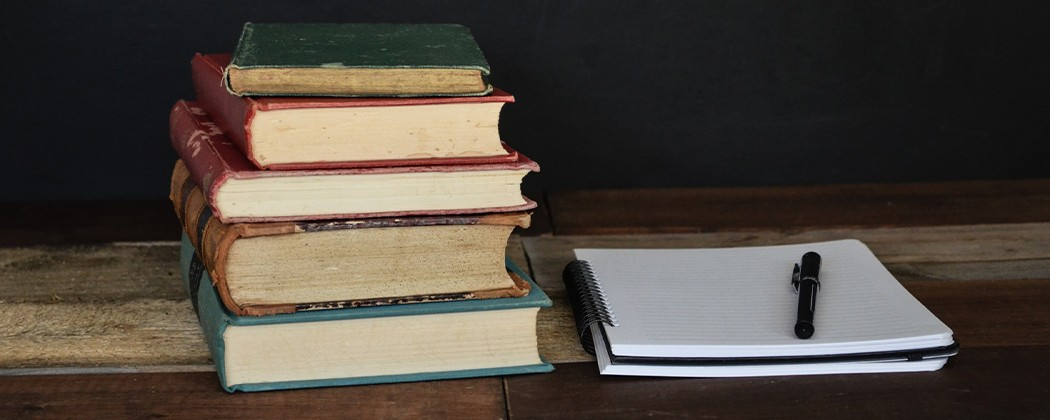 Stack of books with notebook and pen