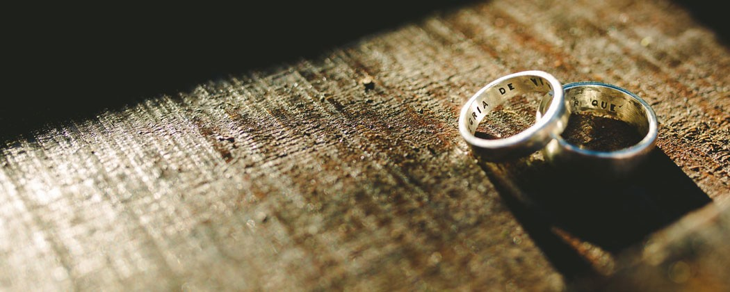 Silver wedding bands on a wooden table