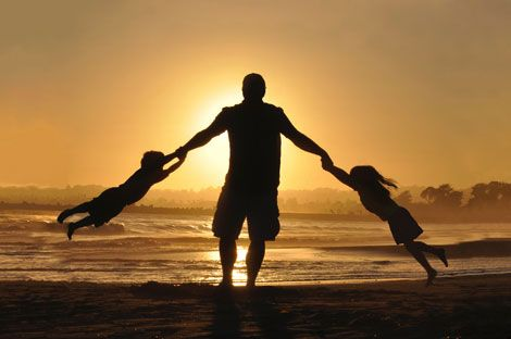 Father holding children on beach at sunset