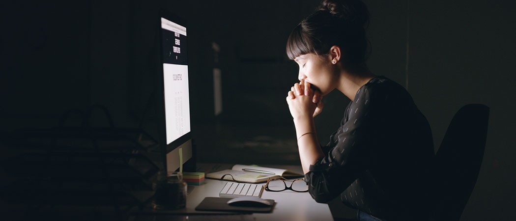 Woman praying at her desktop computer