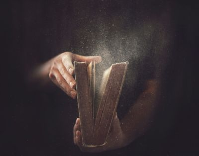 """Man opening a dusty Bible."""