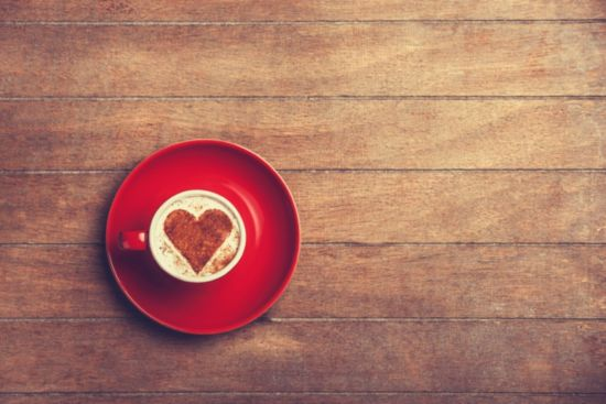 Coffee cup on wooden table with a heart in the cup