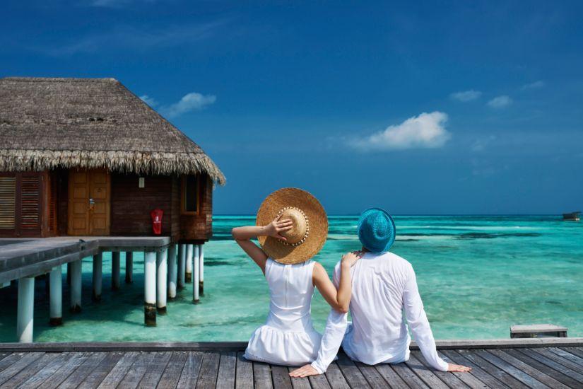 Couple on vacation sitting on boardwalk
