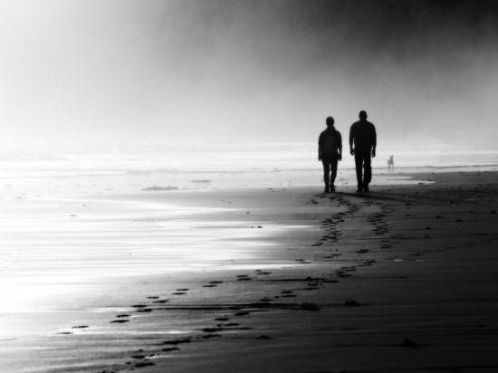 Two men walking on a beach, black and white photo.