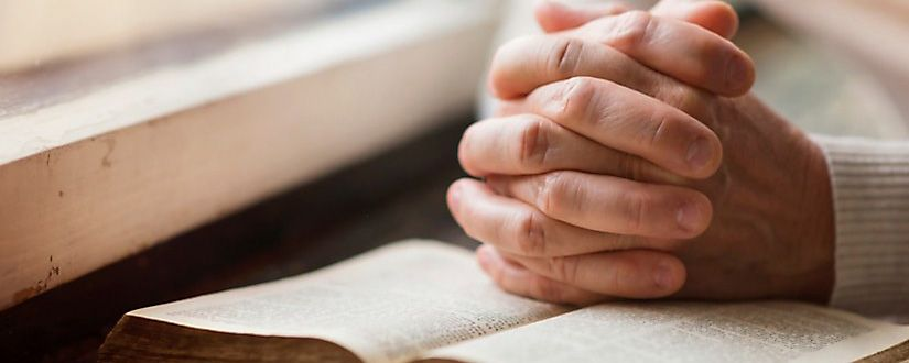 Hands clasped on a Bible