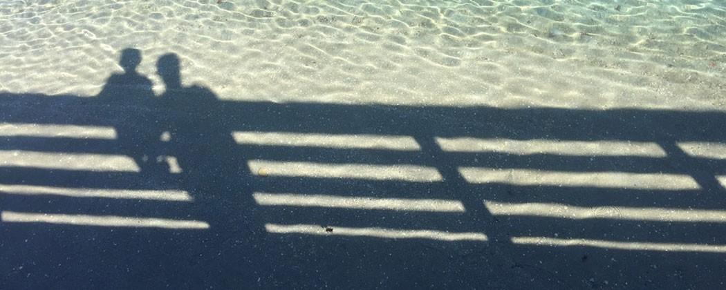 People's shadow overlooking water