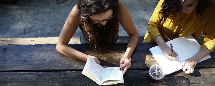 Two women talking and journaling