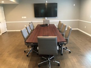 A conference room with a flat screen tv on the wall and a conference table surrounded by beige Harper mid-back chairs