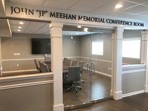 Looking through glass doors at an empty John 'JP' Meehan Memorial Conference Room with a conference table surrounded with Harper Mid-Back Chairs