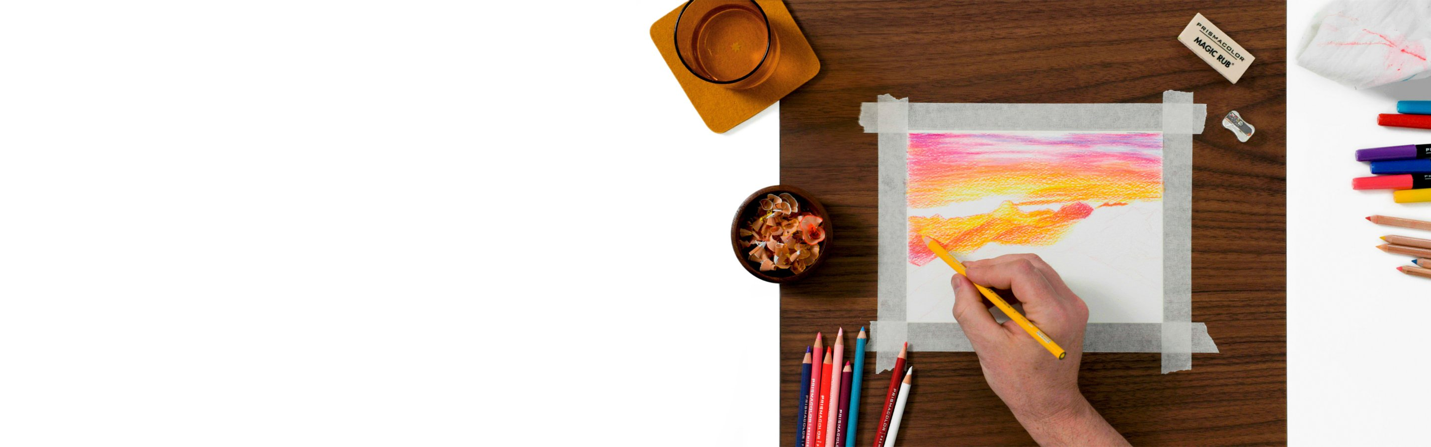 coloring a landscape with colored pencils and other art supplies nearby