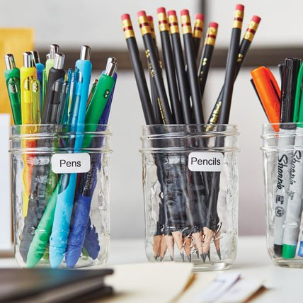 Labeled jars of pens, pencils and markers.