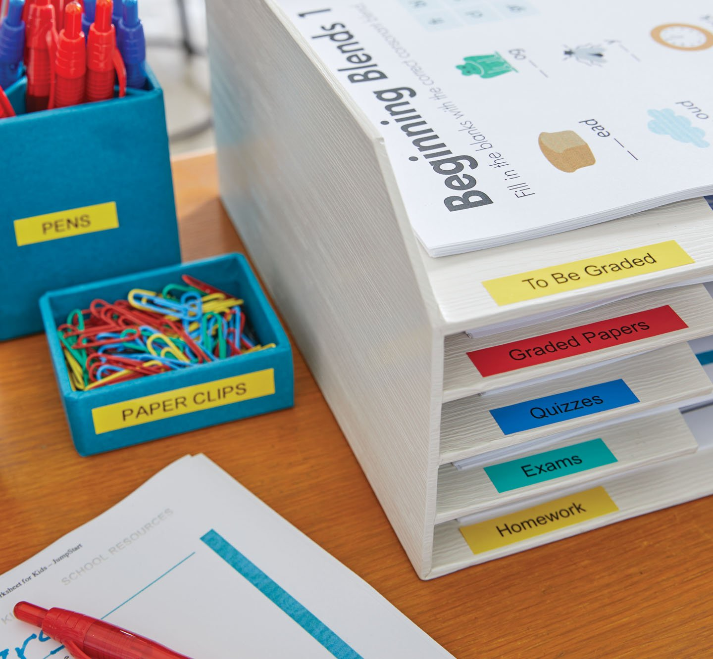 A desk with colorful labels on a desk organizer, paper clip holder and pen holder.