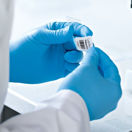 A medical professional placing a barcode label on a glass slide.