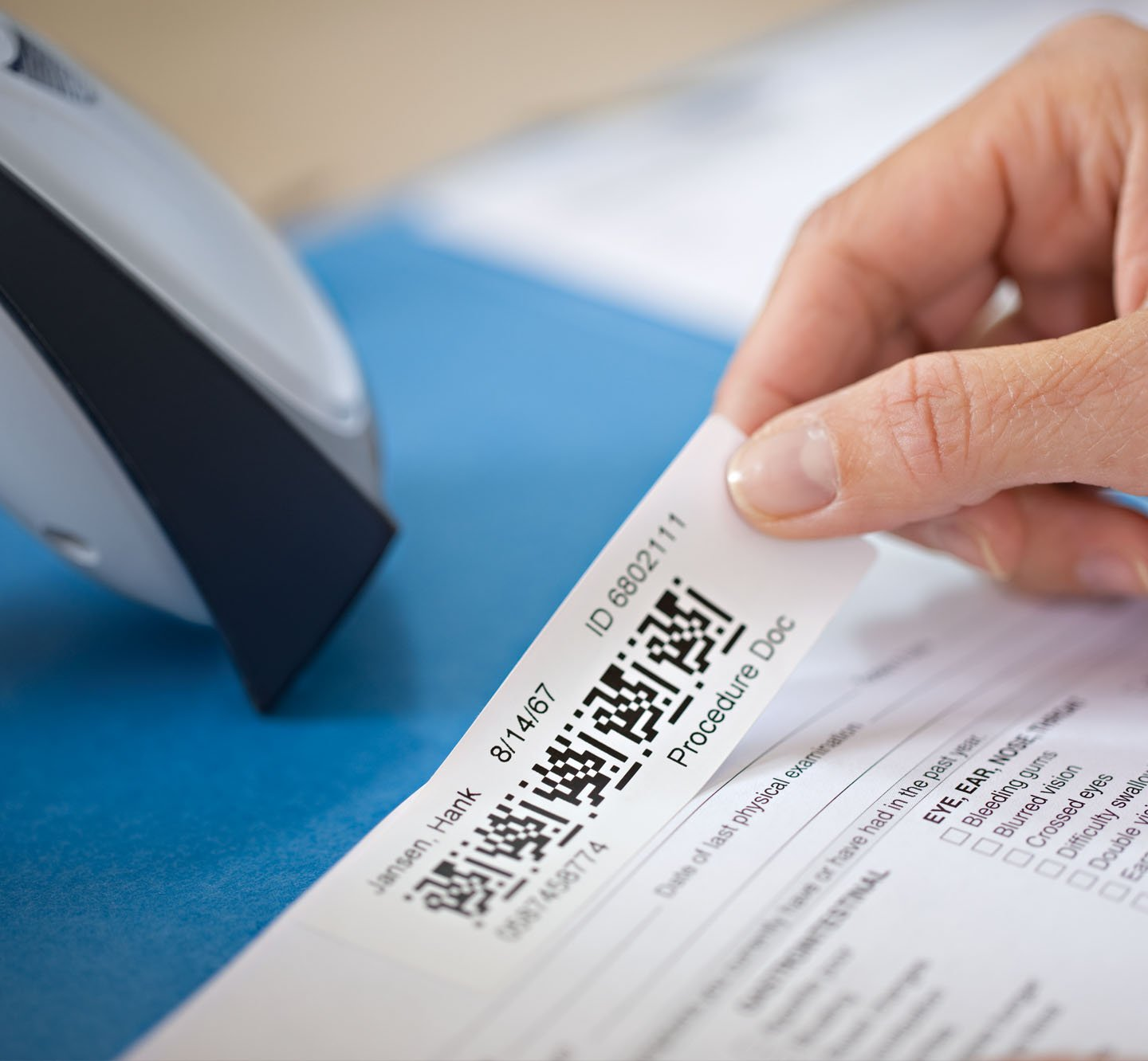 A hand applying a Q R code label to a document.