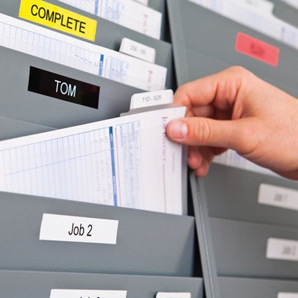 A hand placing a file into a labeled file holder.