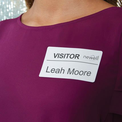 A woman wearing a visitor name badge.