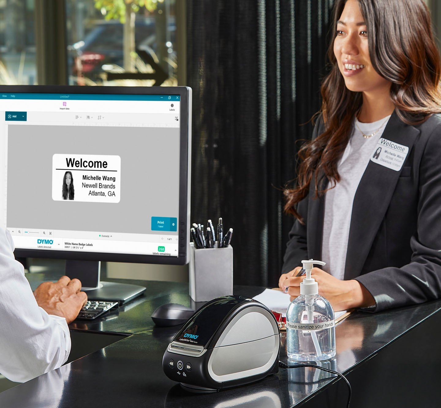 A person using a computer to create and print a welcome label for a visitor.