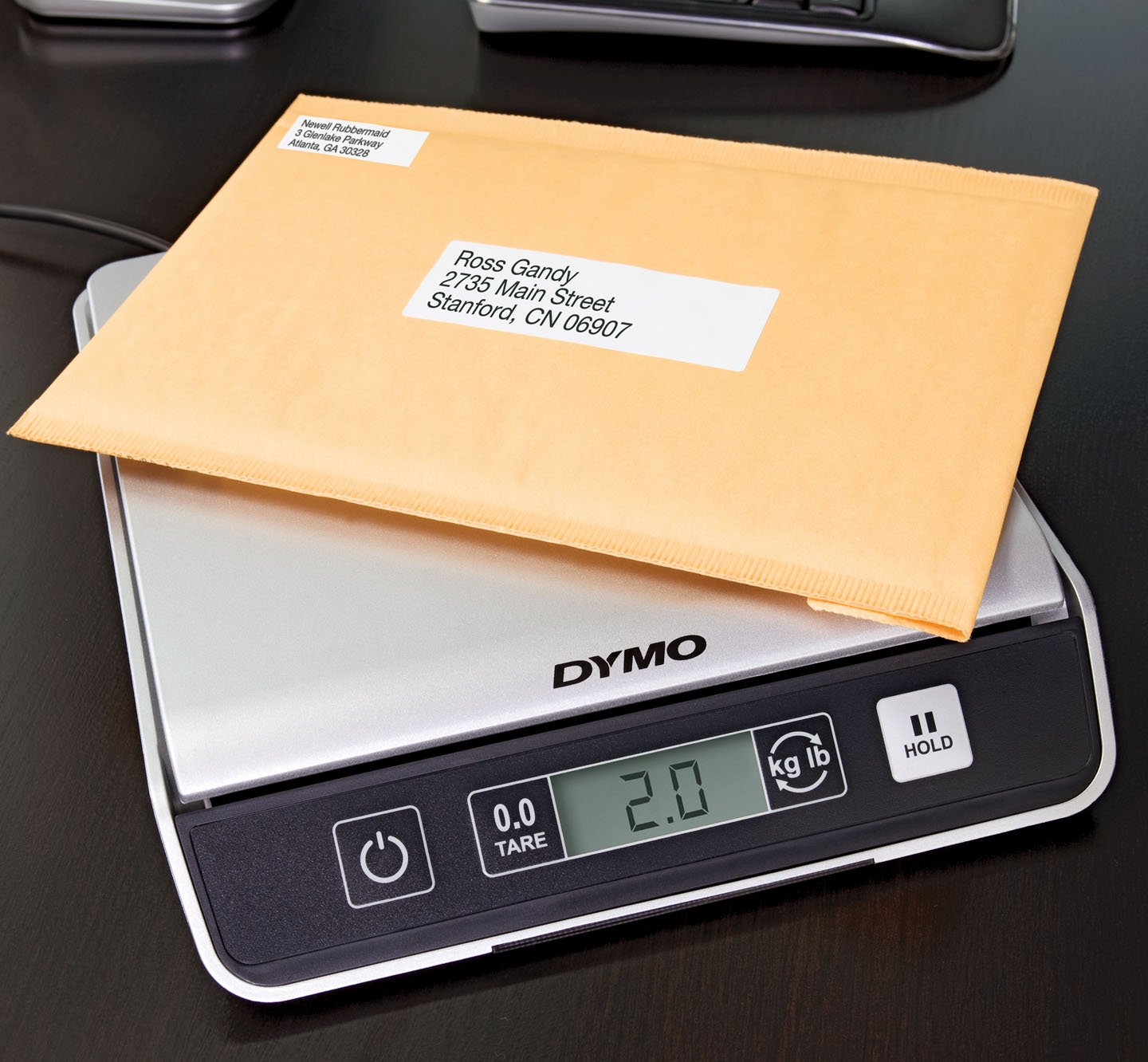 A labeled package being weighed on a scale.