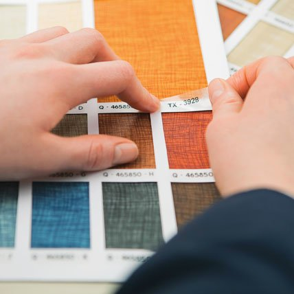 Hands adding labels to color swatches.