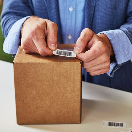 A person placing a barcode label on a package.