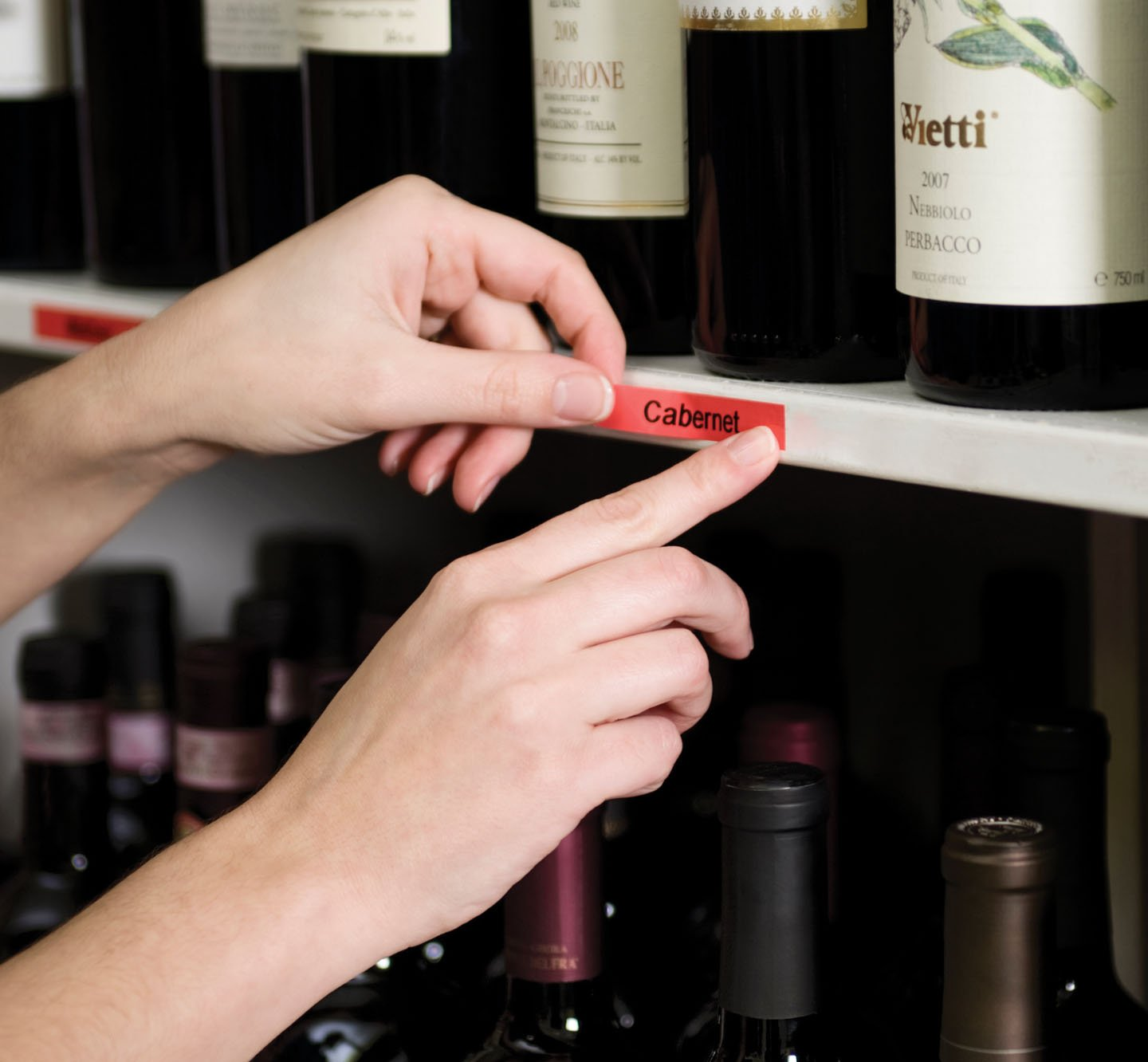Hands placing a red label on a shelf of wine.