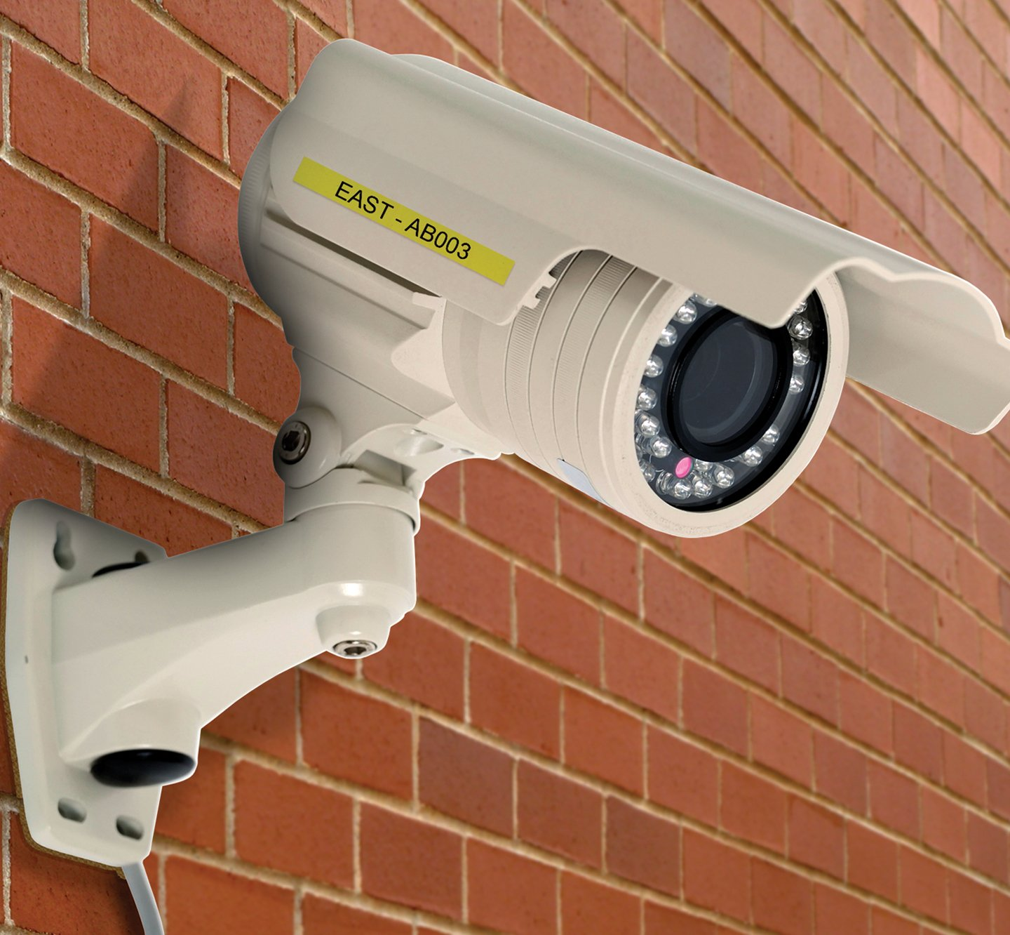 A labeled security camera mounted to a brick wall.