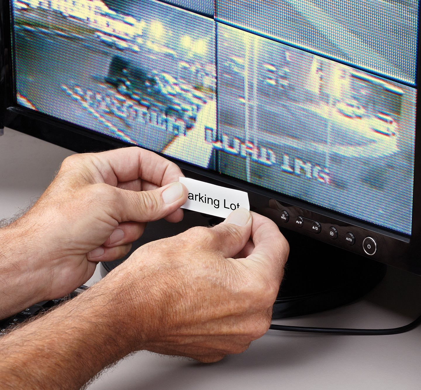 Hands placing a label onto a security monitor.