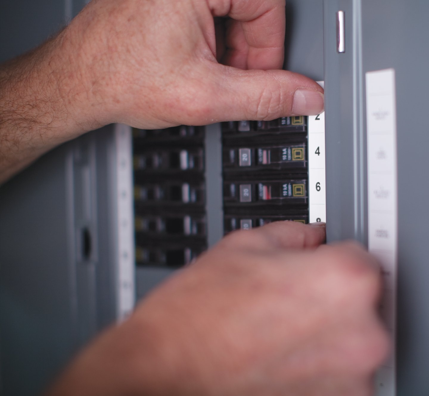 Hands placing a label onto a fuse box.