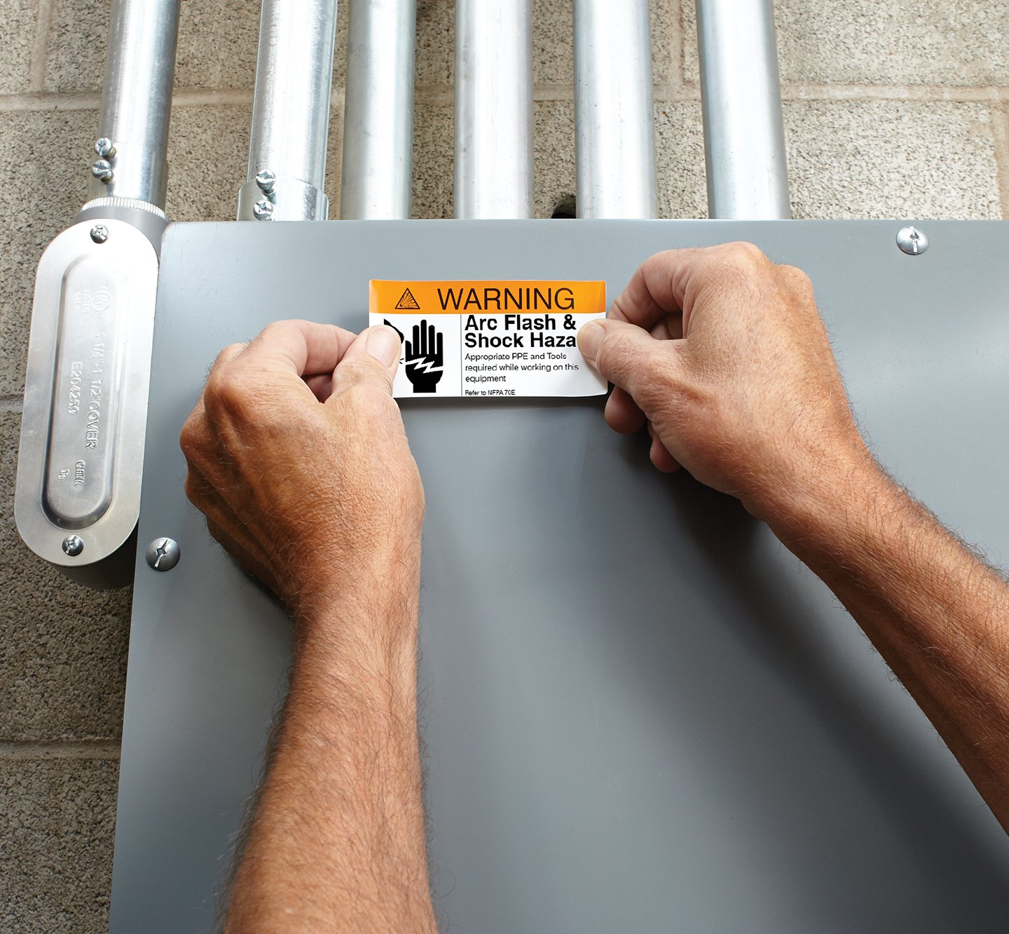 Hands placing a warning label on an electrical box.
