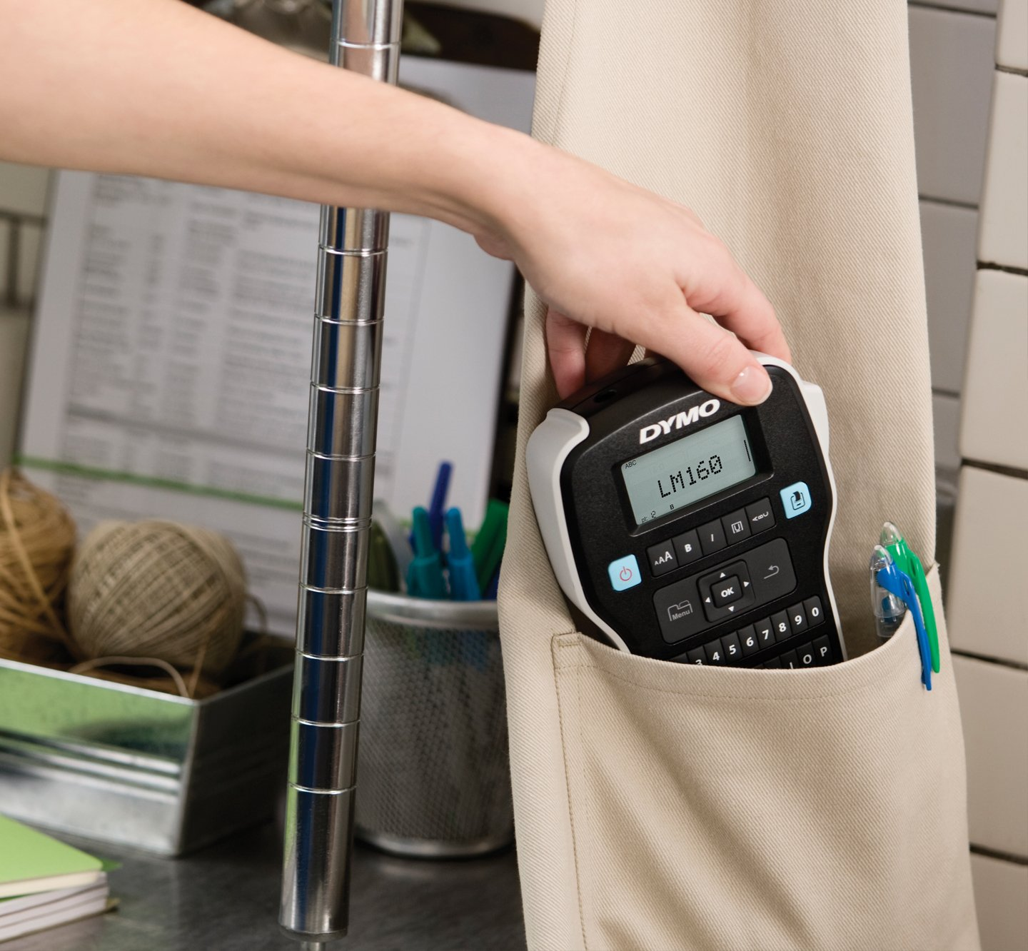 A hand placing a label manager 160 into an apron.