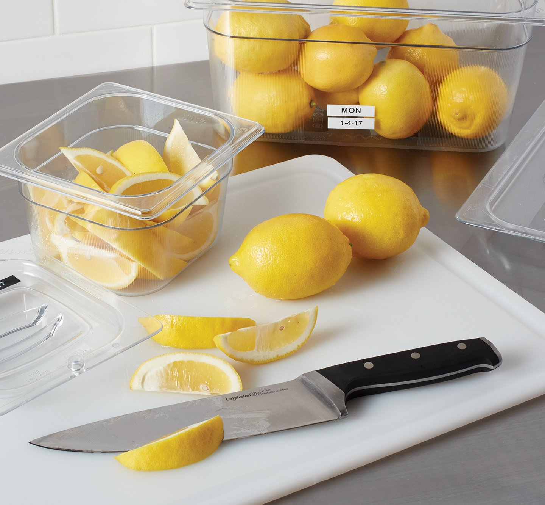 A labeled bin of lemons near a chopping board.