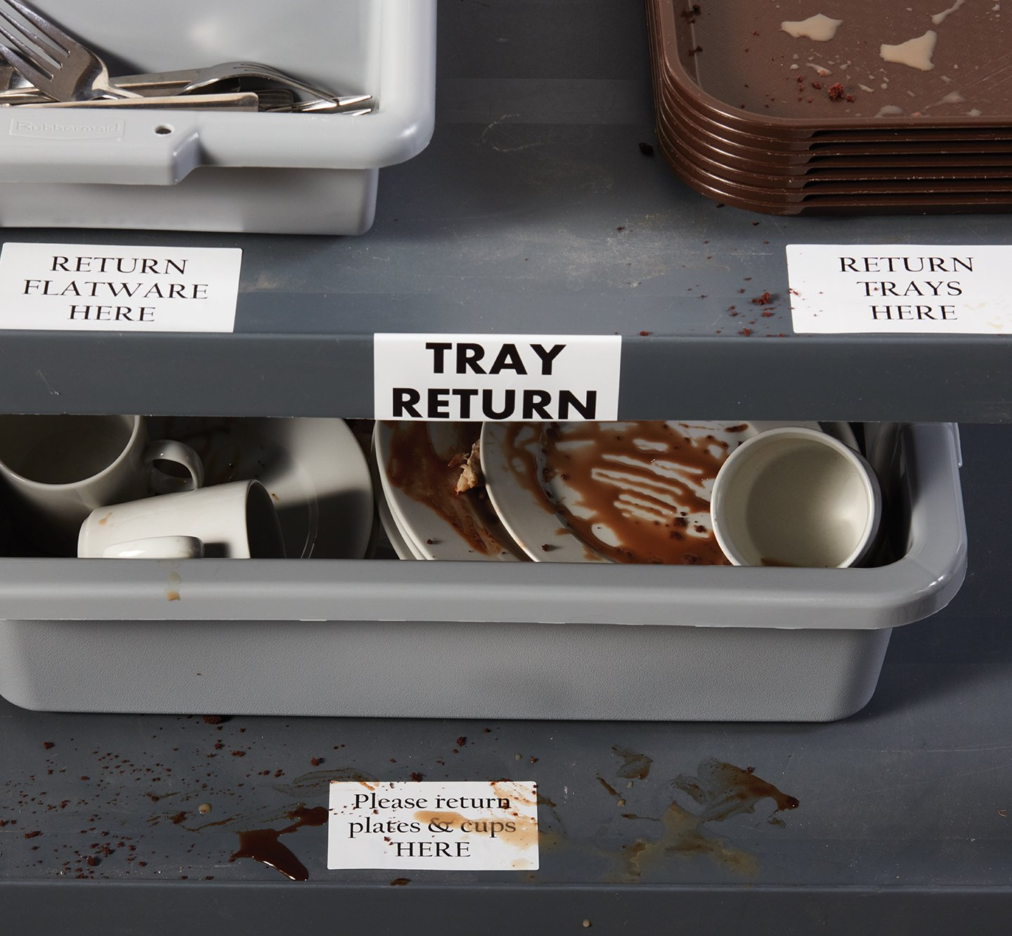 Soiled labels at a restaurant tray return area.