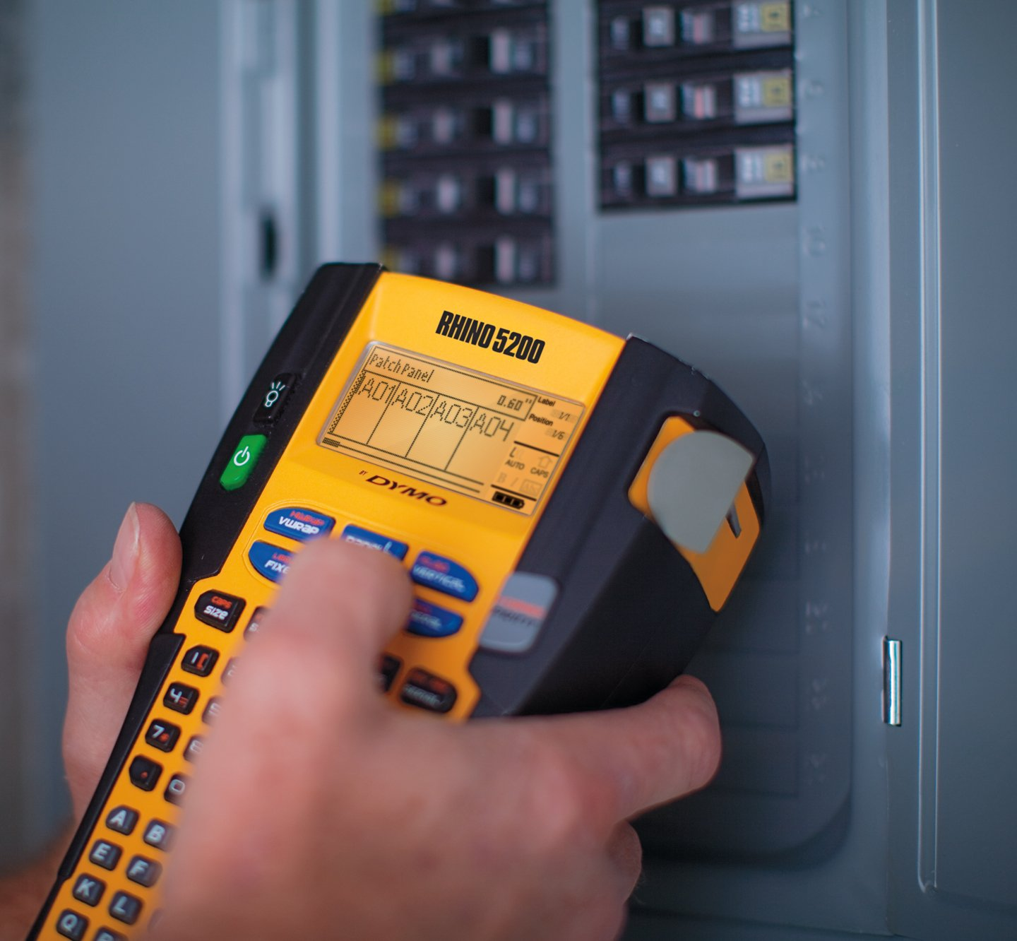 A person using a Rhino 5200 to create labels for a patch panel.