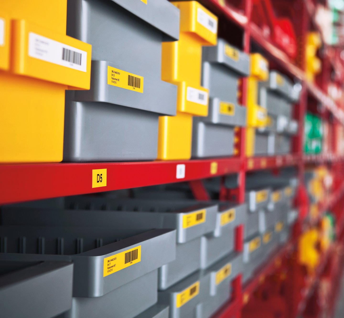 Rows of plastic bins with white and yellow barcode labels.