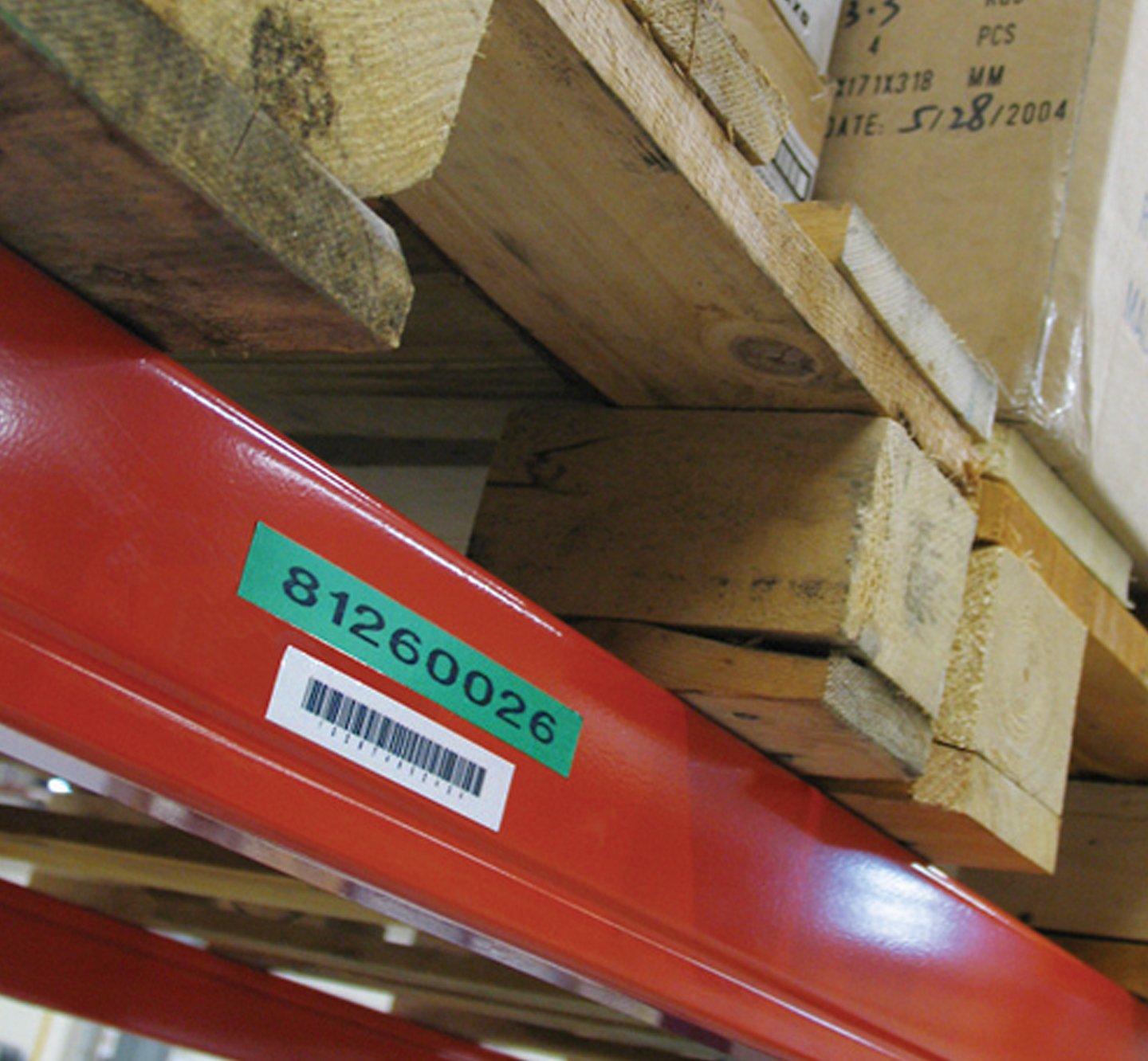 Wooden pallets on a warehouse shelf with a barcode label.