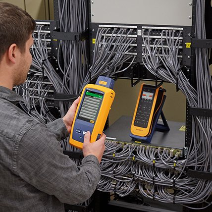 A man using an X T L label maker to create a label for an electronic wiring panel.