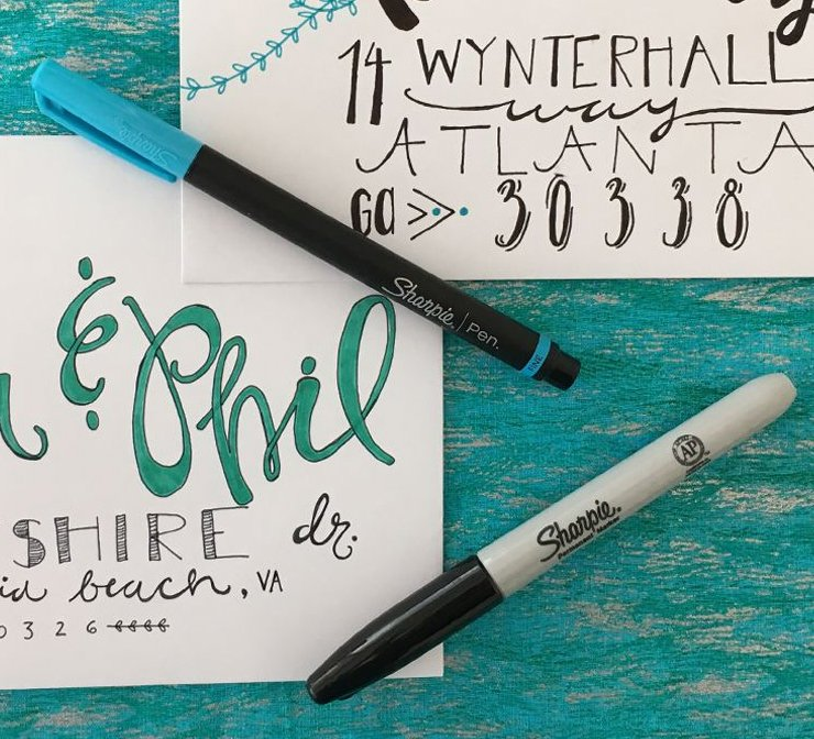 Sharpie marker and pen next to hand made invitations