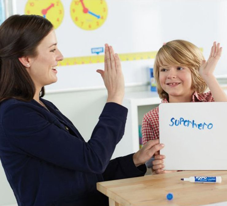 teacherhighfivingstudentholdingexpowhiteboardwithsuperherowritteninblueexpomarkertile.jpg
