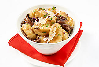 Gnocchi with mushroom and red wine sauce, garnished with Parmesan