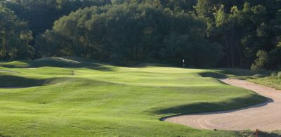 The green of hole 10 on the River course with trees in the background and sandtrap on the right.