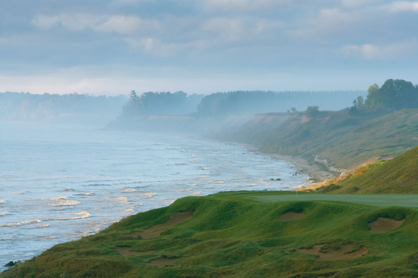 The Lake Michigan shoreline with light fog and waves next to the Straits Course.