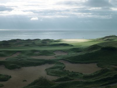 The green of hole 15 of the Straits Course in the distance with Lake Michigan in the background.