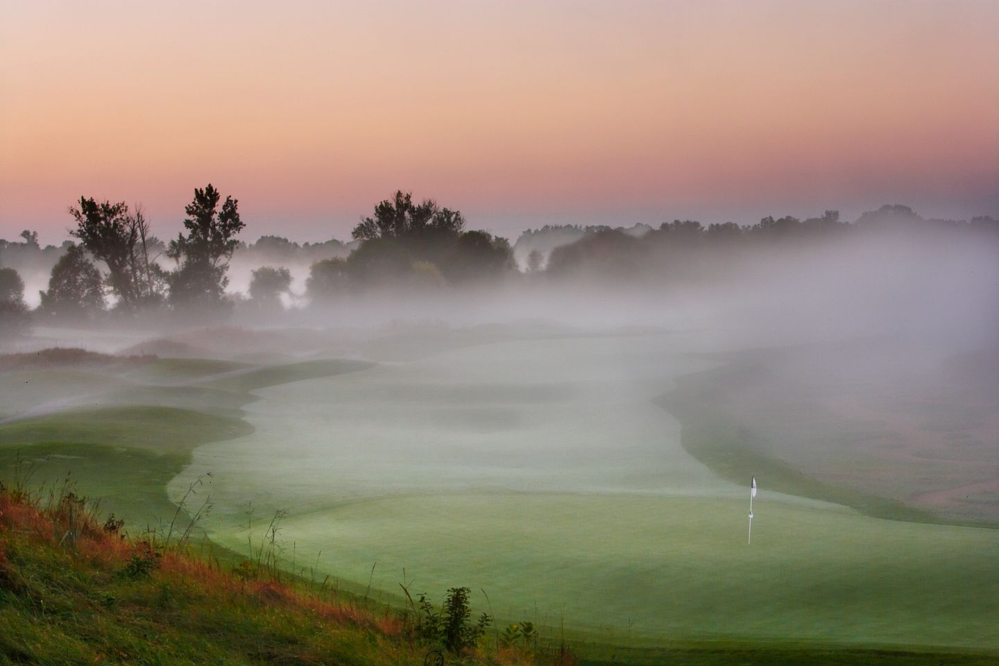 The green of hole 18 on The River Course with the fariway in the background and fog.