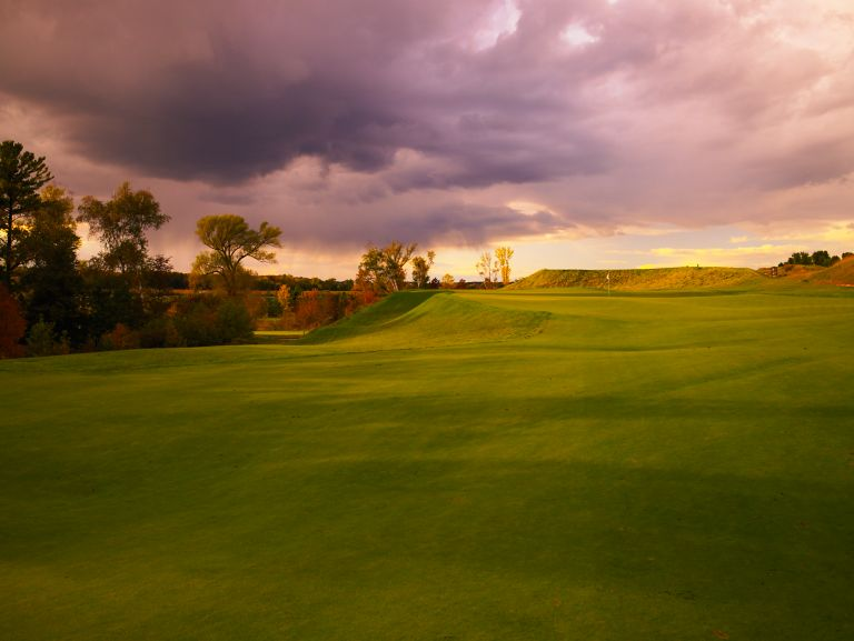 A view of the green of hole 12 on the Irish course with clouds and sun.